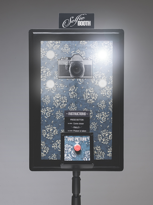 The finished Selfie-Booth (photo booth) in retro style with illuminated button and lights. The DIY photo booth is build around a GoPro Hero 3+ Black Edition camera and triggered by wired remote using timed circuits.
